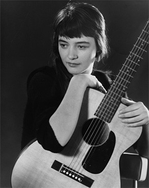 Karen Dalton and her guitar strike a pensive mood.