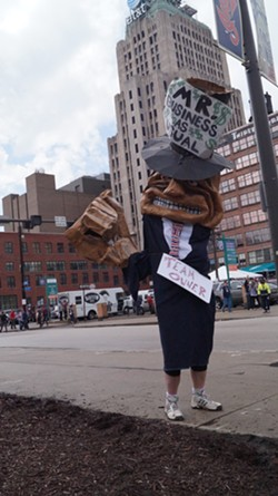 """Mr. Business as Usual,"" a CAST puppet outside Progressive Field at the Cleveland Indians' home opener. - SAM ALLARD / SCENE"