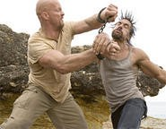 Steve Austin (left) reacts predictably to Manu Bennett's bad hair.