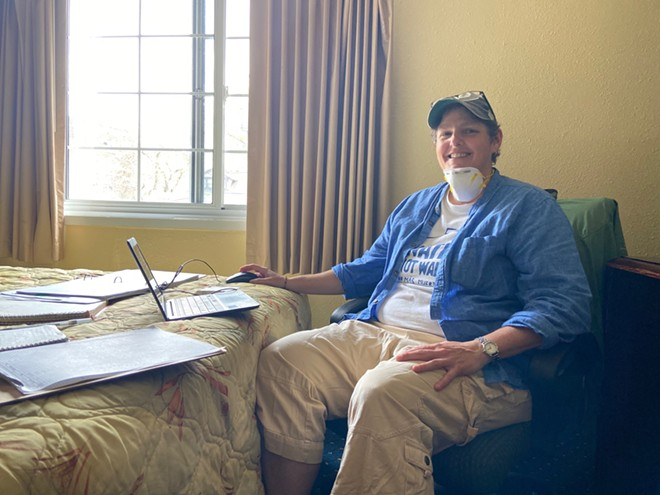 Paula Miller, who has been a Catholic Worker for two decades, uses a hotel room as her office as she coordinates hospitality and outreach efforts for about 50 unsheltered people staying at the hotel for Northeast Ohio Coalition for the Homeless.