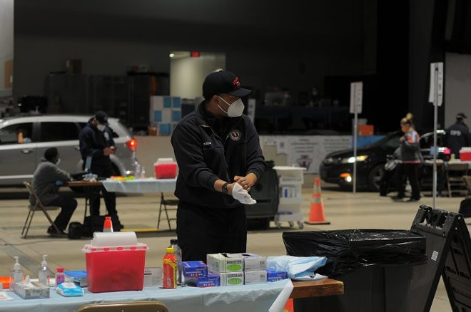 A Columbus Fire Department member dons gloves while working at a mass vaccination site at the Celeste Center in Columbus - PHOTO BY JAKE ZUCKERMAN