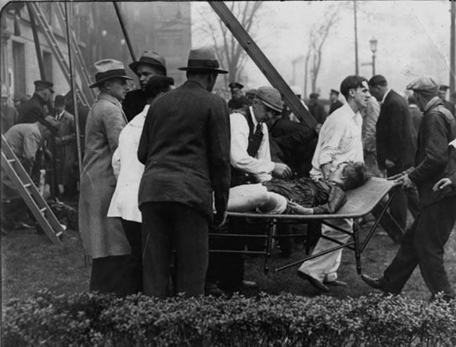 Officials assist a victim of the 1929 fire - CLEVELAND MEMORY PROJECT
