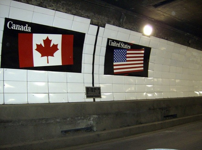 Flags of Canada and the United States over a metal boundary marker in the Detroit-Windsor Tunnel. - MIKERUSSELL, WIKIMEDIA COMMONS