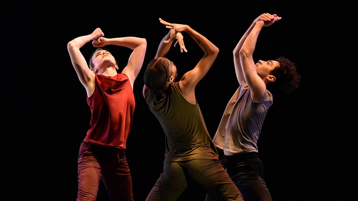 3 Dancers in a circle with their hands in the air.