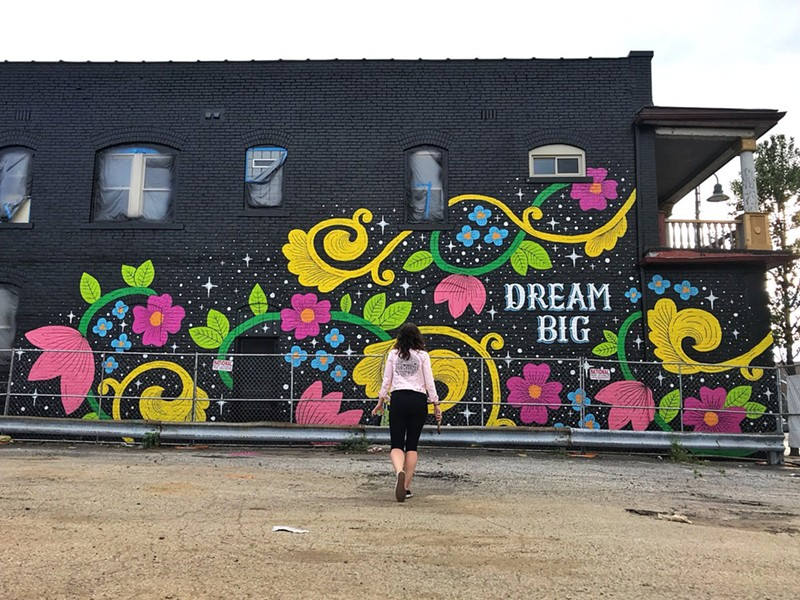 Lisa Quine stands in front of her mural in Gordon Square - TWITTER