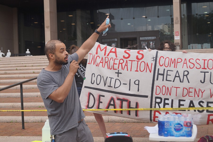 Speaker Dave Okpara gestures to the incarcerated in the county jail; Rally for Justice for Incarcerated Individuals, Cuyahoga County Justice Center, (5/29/20). - SAM ALLARD / SCENE