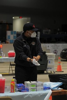 A Columbus Fire Department member dons gloves while working at a mass vaccination site at the Celeste Center in Columbus