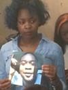 A family member holds a photo of Luke Stewart.