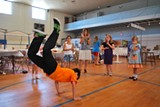 A member of 'Ta Pedia' performs a distinctive dance move during rehearsal as Stamata Karfakis claps to the beat