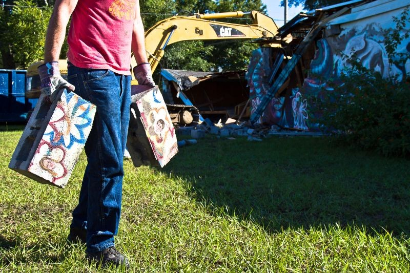 Artist Matt Hebermehl hauls off the remnants of the mural on Habersham and 34th streets. - JON WAITS/@JWAITS