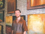 Brian MacGregor in front of some of his artwork.
