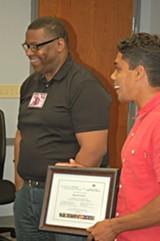CRI Life Enhancement Core Team member Palmer Severson (right) presents Reginald Franklin with his program graduation certificate at the end of the 12-week program.