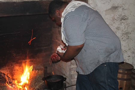 Culinary historian (= 'culinarian') Michael W. Twitty tended hearth at Wormsloe Historic Site during last week's Slave Dwelling Conference. Photo by Teri Schell