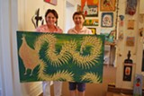 Michelle Harris of Saskatoon (right) and Roots Up owner Leslie Lovell stand with Steve Burnley's folk art chicken painting.