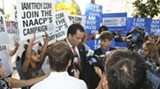 NAACP President Ben Jealous and Amnesty International Executive Director Larry Cox surrounded by sign waiving supporters at a press conference in Wright Square before the hearing began June 23. (Photo: Patrick Rodgers)
