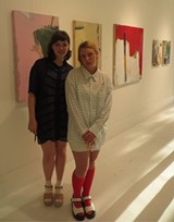 Non-Fictioners Alessandra Hoshor and Alycia Linke stand before a group of paintings by Jane Winfield.