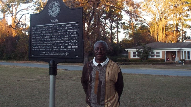 Norman Luten, Jr. is shown at the Sandfly historic marker erected in 2003.
