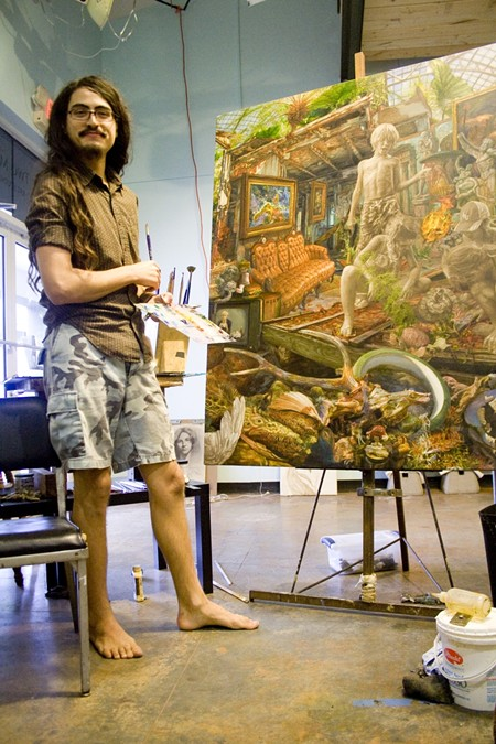 Painter Isaac McCaslin in his Starland District studio working to complete his final piece for the Telfair Art Fair this weekend.