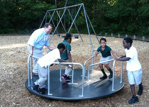Savannah Alderman Tony Thomas and neighborhood children test ride some of the equipment at the new Crusader Park Neighborhood Center Playground