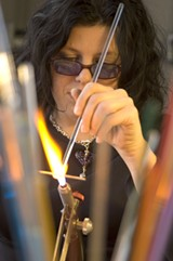 Self-taught artist Amber Higgins handcrafts sparking, multi-colored glass pendants.