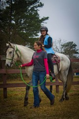 Sidewalker Lynn Thompson leads 11 year-old Kaleigh on a ride with Tom Sawyer, an Aztec pony that provides equine therapy.