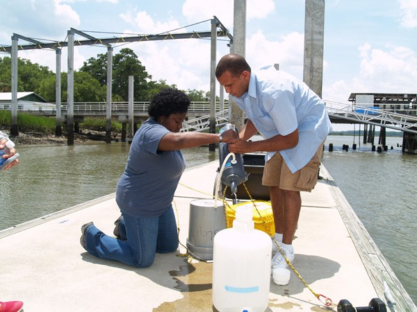 Skidaway Institute's LaGina Frazier and Kevin McKenzie transfer a water sample from a collection bottle to plastic storage jug.