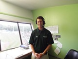 Toby Hyde is a man of many voices, also announcing SSU football and baseball games. Here he is in the familiar green-tinted press box overlooking the infield at Grayson Stadium. Photo by Orlando Montoya
