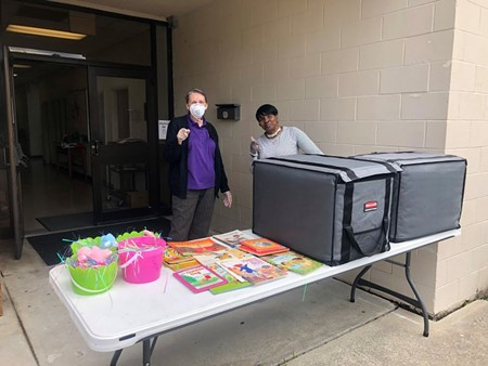 Salvation Army volunteers prepare to distribute books and meals to families in need.