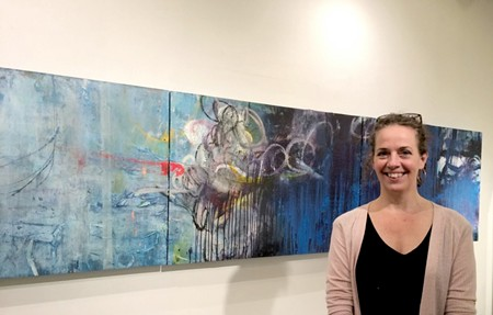 "Deb Oden, painter, printmaker and co-curator of ""The Industry,"" stands before her contribution to the Kobo Gallery exhibition."