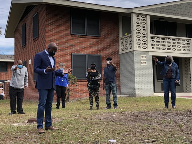 Rev. Raphael Warnock, in foreground at left, prays with supporters in front of Savannah's Kayton Homes housing project during a campaign visit  on Dec. 12. - NICK ROBERTSON/CONNECT SAVANNAH