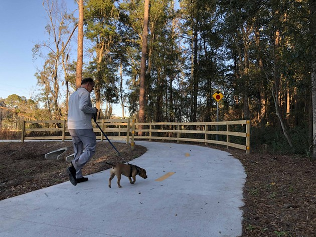A man walks his dog on the newly completed Truman Linear Park Trail. - NICK ROBERTSON/CONNECT SAVANNAH