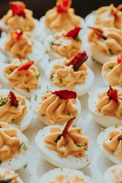 Guests are offered deviled eggs during an event April 16 at New Realm Brewing. - PHOTO BY LINDY MOODY
