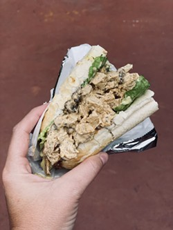 A patron showcases the curry chicken salad sandwich from Zunzi's, bought at their new location on Drayton St. - PHOTO BY LINDY MOODY