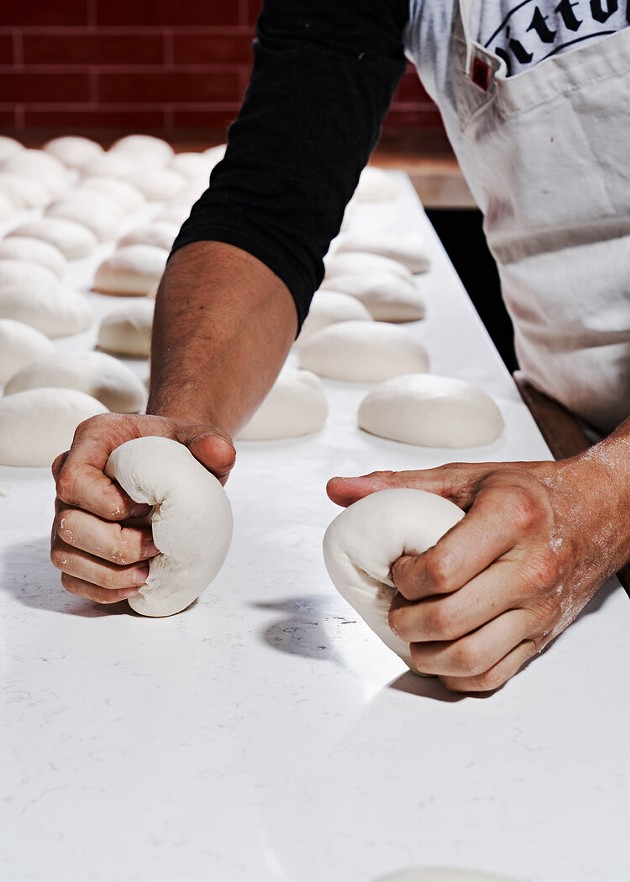 A chef creates dough for pizzas at Pizzeria Vittoria in Starland Yard. The restaurant turned two-years old this month. - PHOTO COURTESY OF PIZZERIA VITTORIA