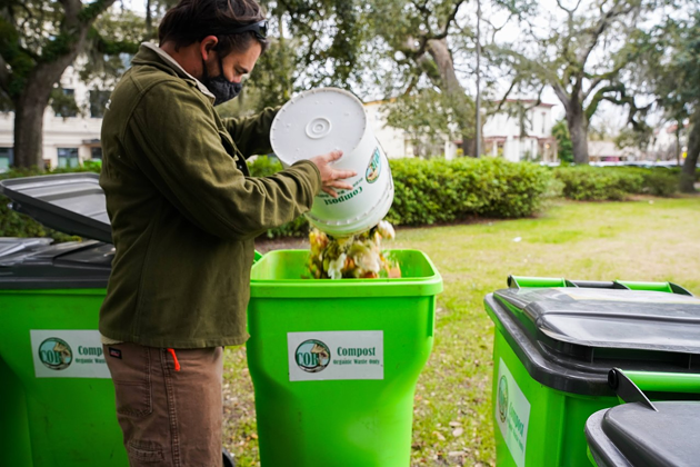 Michael Wedum dumps a bucket of compost into one of the new Code of Return Compost bins. - PHOTOS COURTESY OF CODE OF RETURN COMPOST