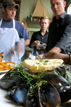 Chef David Landrigan, left, and company enjoy some of their kitchen's handiwork, in this case the amazing mussels. - PHOTO BY MELISSA DELYNN