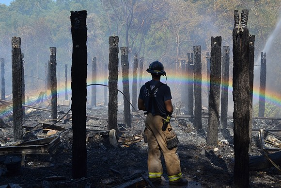 Advanced Firefighter Andrew Jones looks out over the smoldering remains of a building on E. President St.
