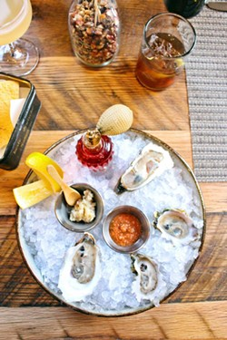 Fresh shucked oysters with an antique perfume bottle filled with house made mignonette, peanut horseradish and cocktail sauce.