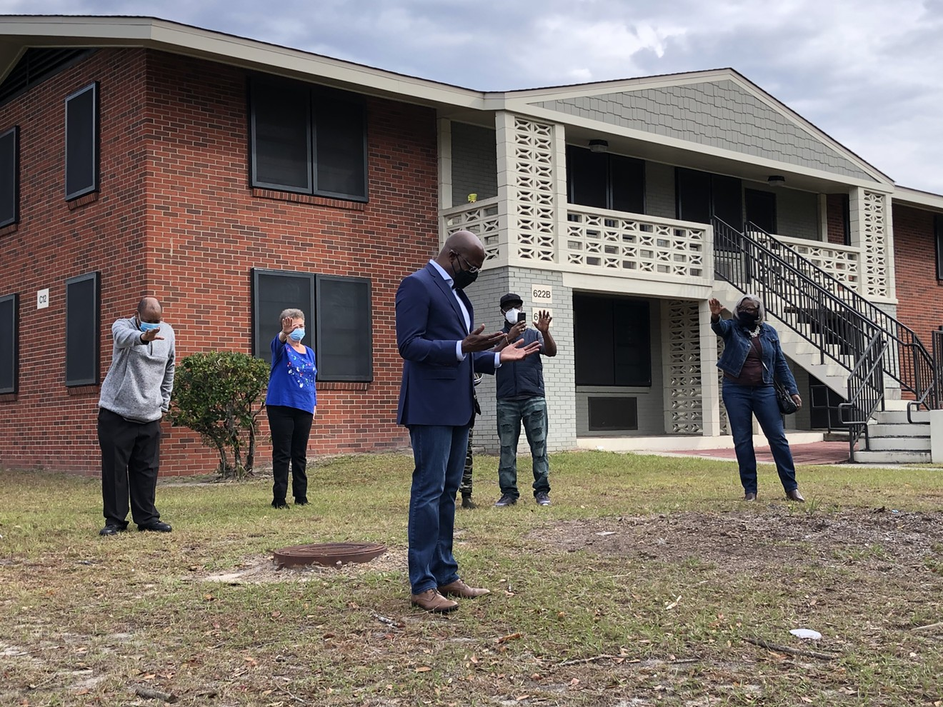 U.S. Senate candidate Raphael Warnock stands in the middle of a prayer circle in front of his childhood home at Savannah's Kayton Homes housing project on Dec. 12.