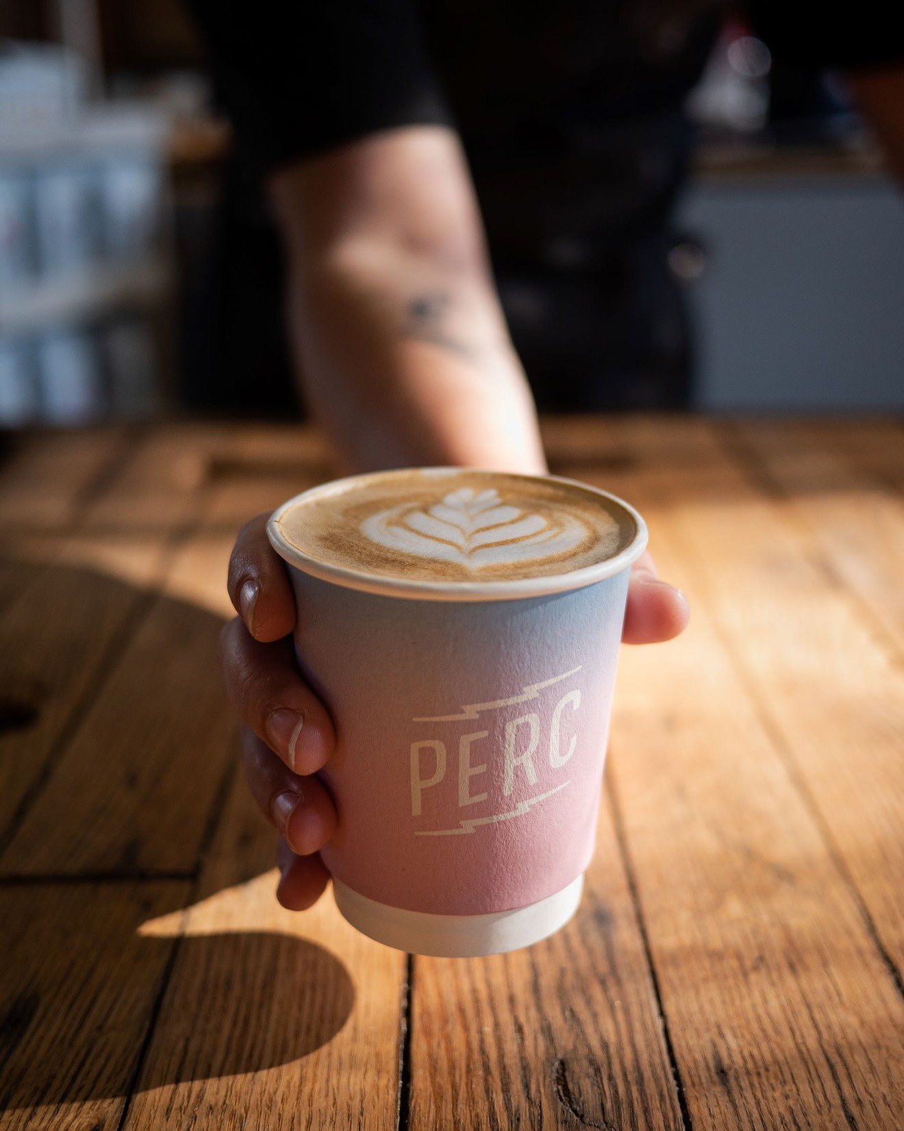 A Perc Coffee team member serves up a latte at one of the Savannah stores.