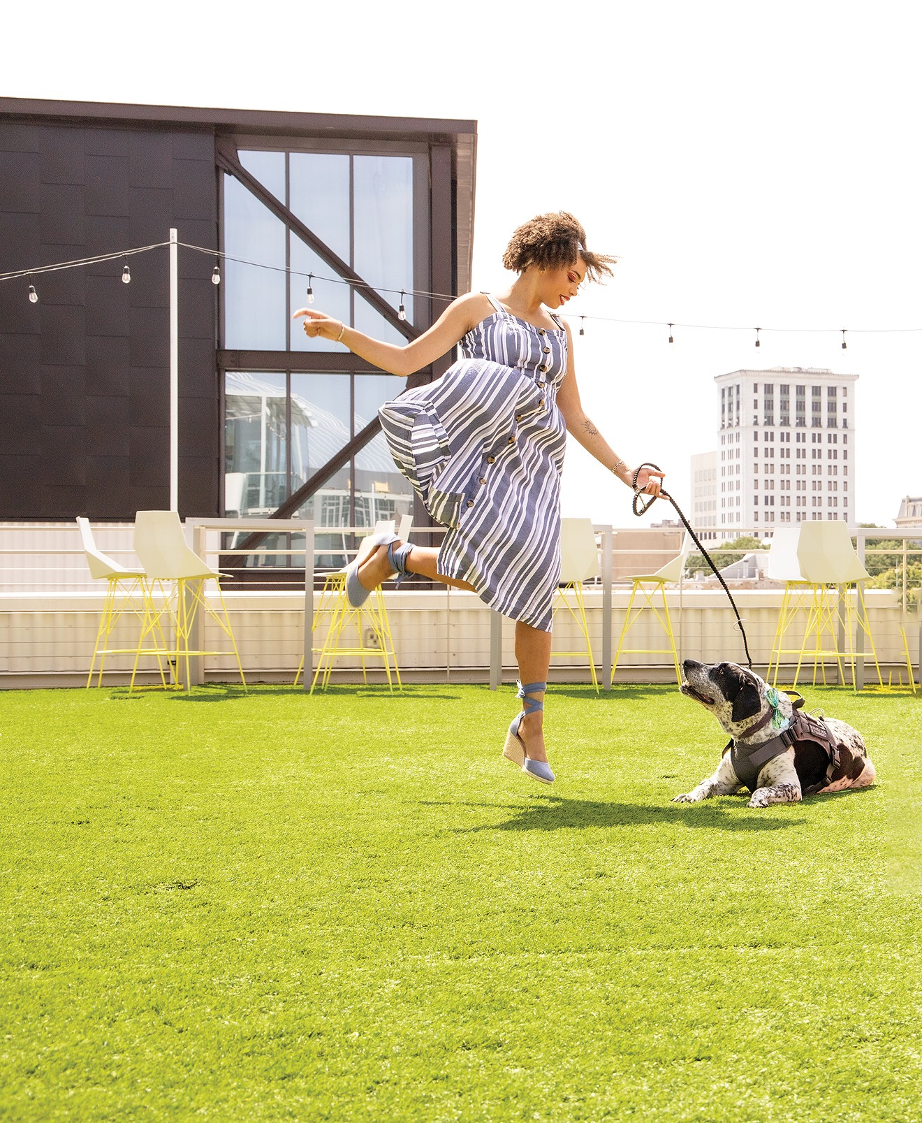 Sadé Harris rejoices on the turf at Electric Moon with her service dog Bambi as she looks forward to the upcoming event, Savannah Carnaval, to be held at Plant Riverside District to benefit the SD Gunner Fund.