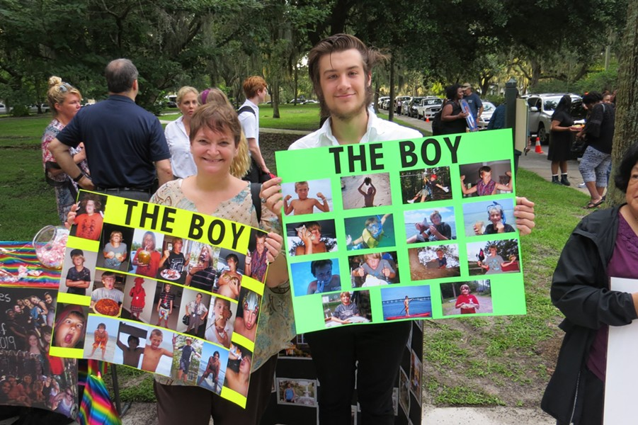Luke Edenfield (a.k.a. The Boy) escorted by his Aunt Melanie on the first day of Senior year and holding posters filled with precious childhood memories.