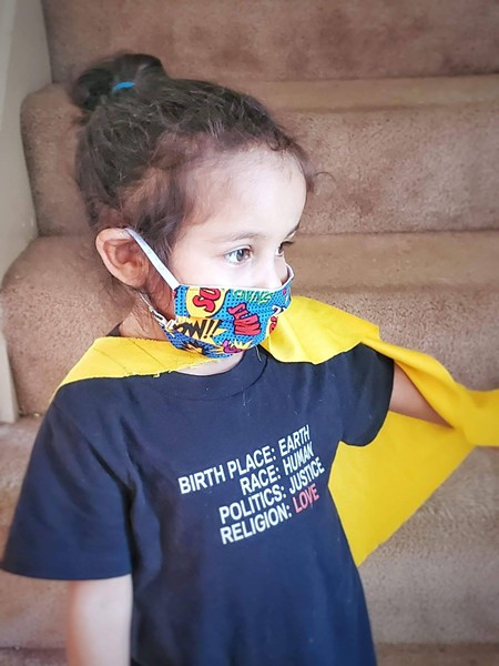 Maya, 3, wears a mask created by her mother Candace Hardnett