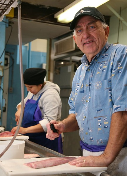 Charlie Russo, Jr. bones up on his knife skills with a local shad, along with employee Blanca Perez. - PHOTO BY JON WAITS