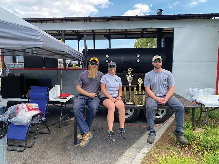 HunniLovins BBQ owners Kevin and Candace Hunnicutt and Brandon McElveen claim their first place title May 15 at the King of the Hog event.