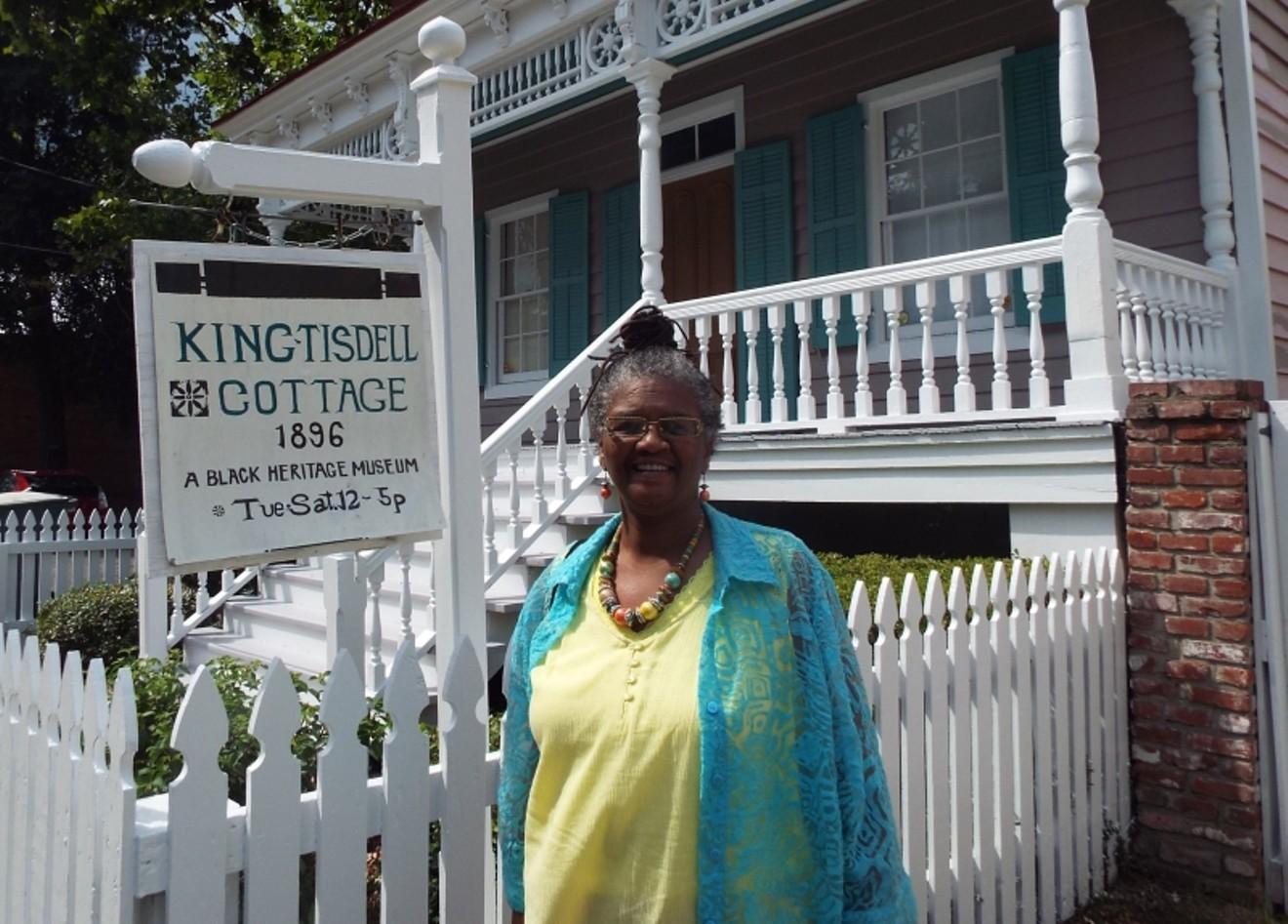 Vaughnette Goode-Walker in front of the King-Tisdell Cottage