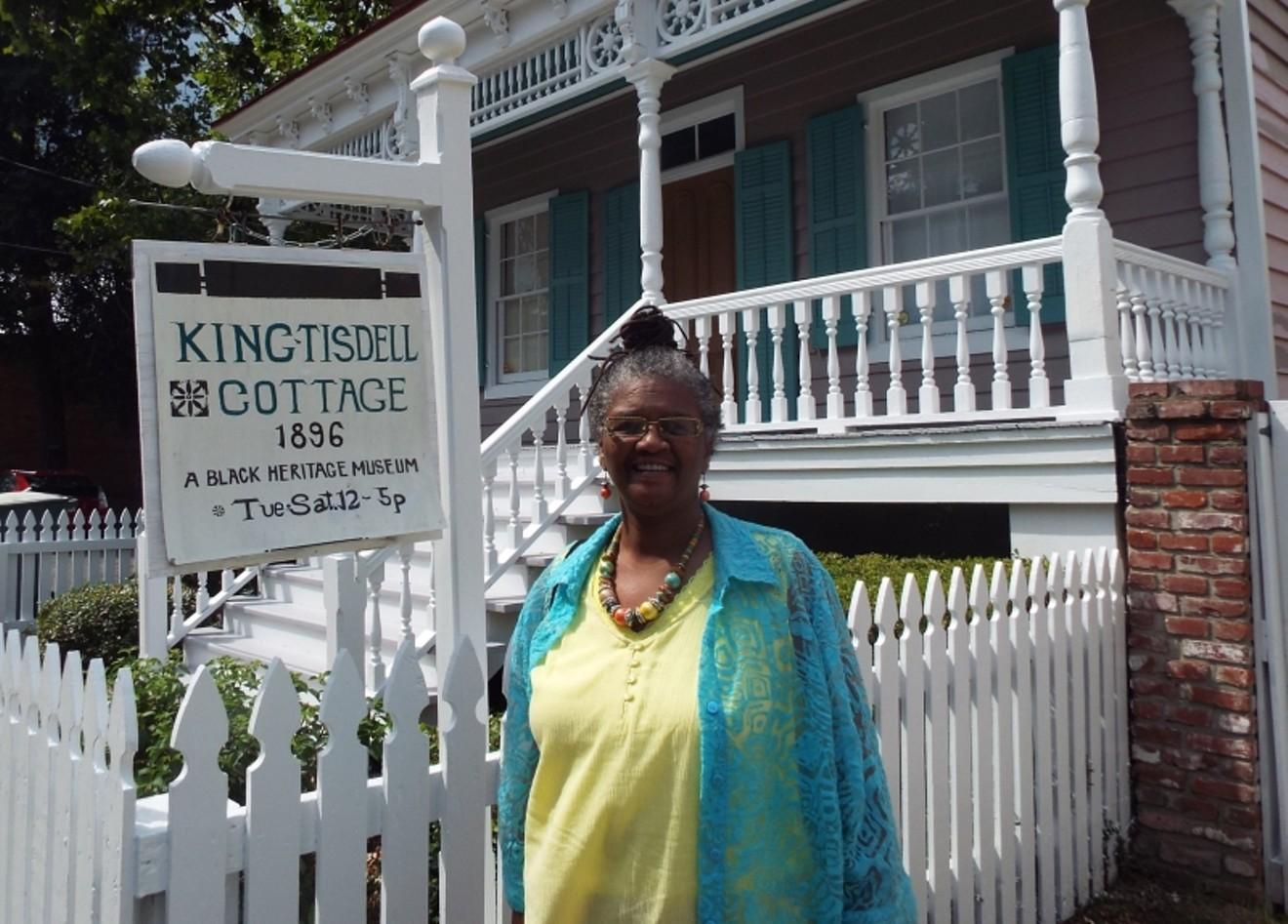 Vaughnette Goode-Walker in front of the King-Tisdell Cottage