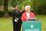 Wilshire Estates resident Bonnie Harris (front) celebrates the groundbreaking of a new community garden with Mayor Edna Jackson and other city officials. The plot was once a vacant FEMA lot.