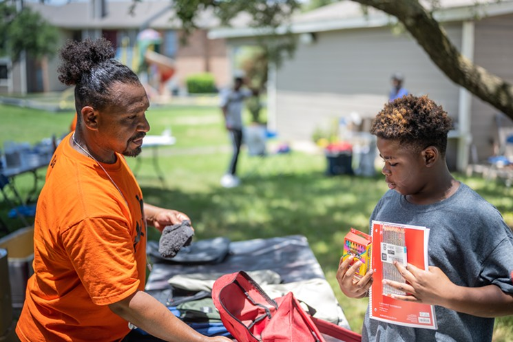 Victor Alvelais offers a young man a backpack and supplies at Chaucer Place Apartments in South Dallas. - MIKE BROOKS