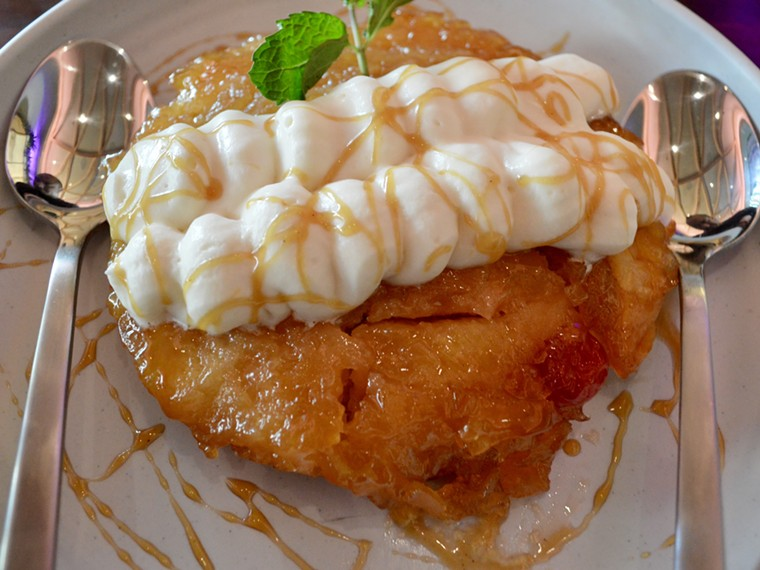 Upside down pineapple cake topped with whipped cream and a caramel drizzle - FELICIA LOPEZ